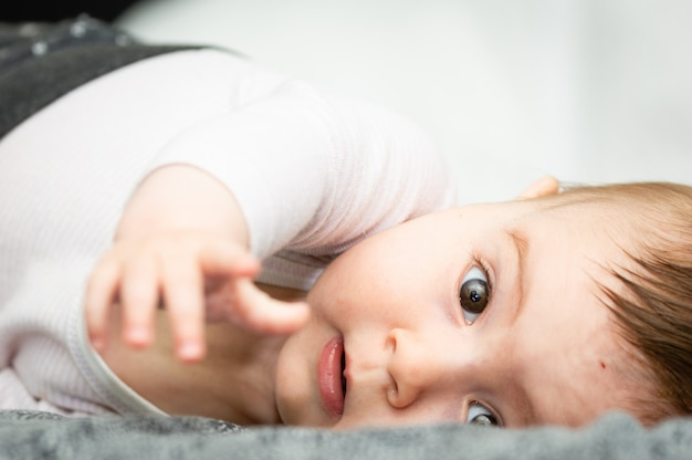 Adorable blond baby lying on his back on the white bed looking directly at the camera.