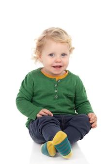 Очаровательны блондинка ребенок сидит на полу изолированные