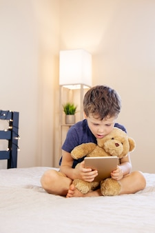 Adorable blond boy sitting on the bed with teddy bear and reading with tablet pc at home indoors child with tablet computer