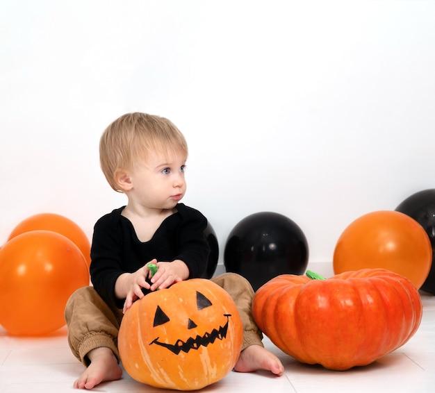 カボチャの装飾の赤ちゃんと愛らしい金髪の白人の幼児がハロウィーンの日を祝うコピースペース