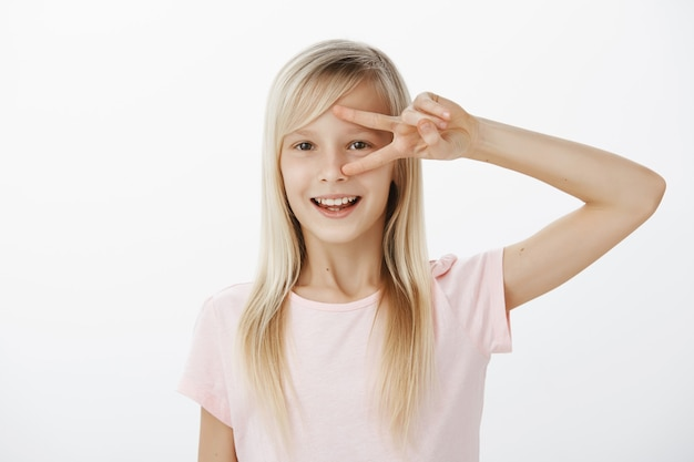Adorabile ragazza bionda con un atteggiamento amichevole che gioca con gli amici e si diverte, mostrando la vittoria o il segno della pace sugli occhi e sorridendo ampiamente dalle emozioni positive sul muro grigio