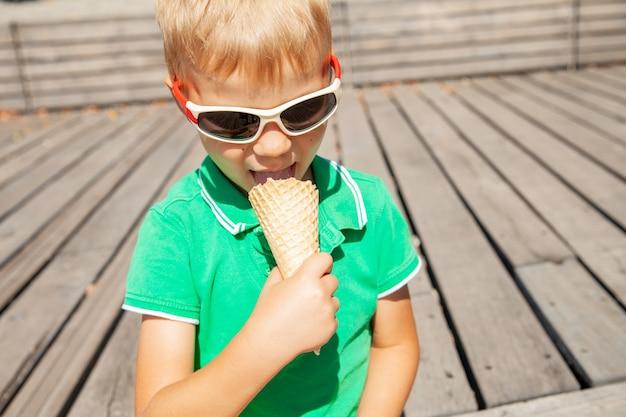 Очаровательный светловолосый маленький мальчик в модных солнцезащитных очках кусает вкусное ванильное мороженое, проводя летний день в парке