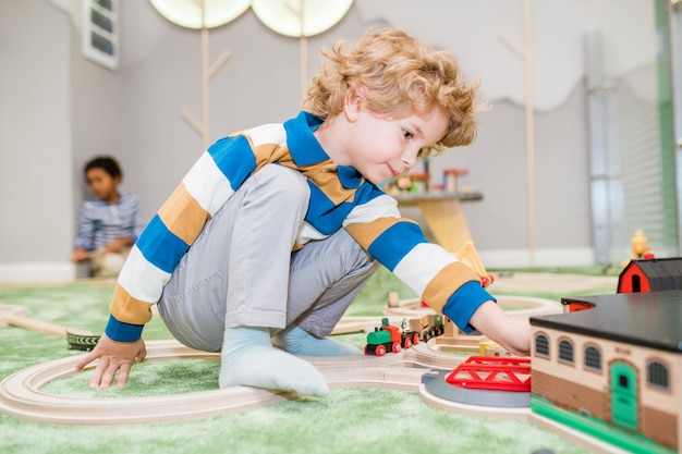 Adorable blond little boy in casualwear playing on the floor with toy trains and house in kindergarten or children center