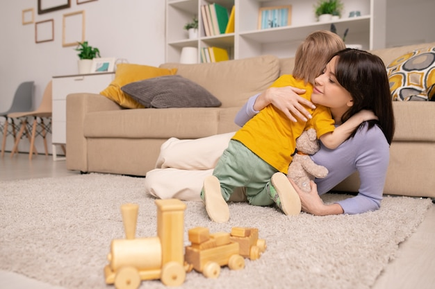 Adorable blond little boy giving hug to his happy mom while both relaxing on the floor by couch at home during period of quarantine