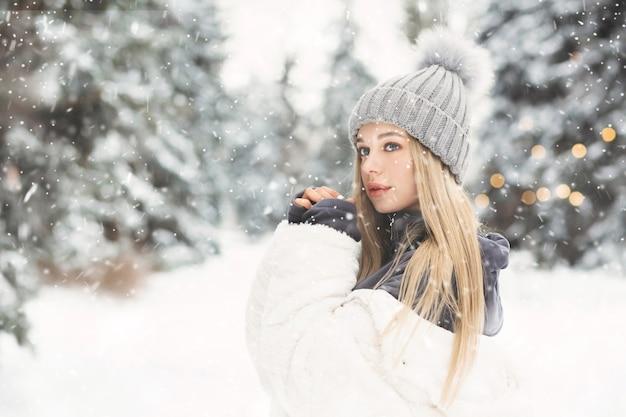 雪の降る天気で森の中を歩く白いコートを着た愛らしい金髪の女性。テキスト用のスペース