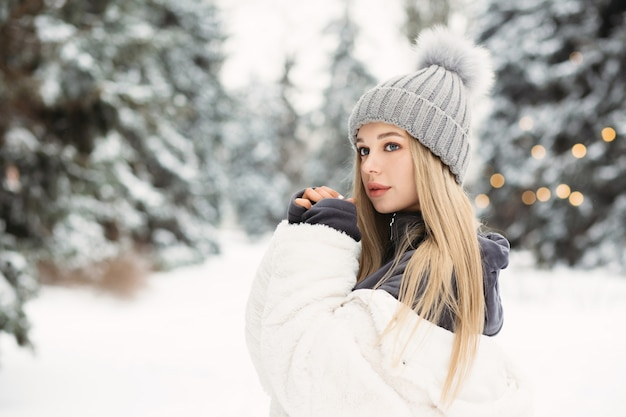冬の森を歩いている白いコートを着た愛らしい金髪の女性。テキスト用のスペース