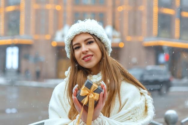 降雪時に通りでギフトボックスを保持している白いコートの愛らしい金髪の女性。テキスト用のスペース