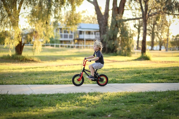 Adorable blonde australian kid riding a small bicycle in the park