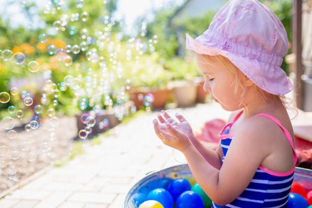 Прелестная белокурая девочка 3-х лет в розовой шапке и синем полосатом купальнике, которая принимает ванну на заднем дворе и играет с пузырьками.