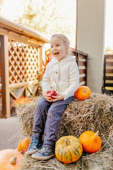 Adorable blonde baby toddler in white knittes jacket sitting on the haystack with pumpkins at porch, playing with apple and laughing