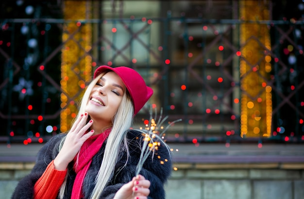 Adorable blonde girl celebrating new year with sparklers at the blurred city lights. space for text