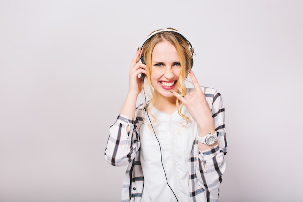 Adorabile ragazza bionda vestita in maglia bianca sorride con aria di sfida, ascoltando musica rock e divertendosi. elegante giovane donna in cuffie che indossa un orologio da polso alla moda mostra segni di metalli pesanti e balli.