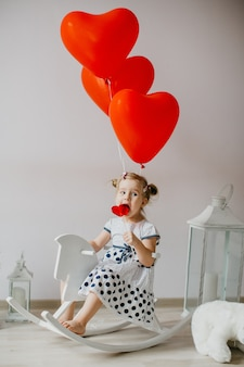 Adorable blonde girl eating a caramel lollypop in the shape of a heart. kid sitting on a white wooden horse with red heart shaped balloons.valentine's day concept.