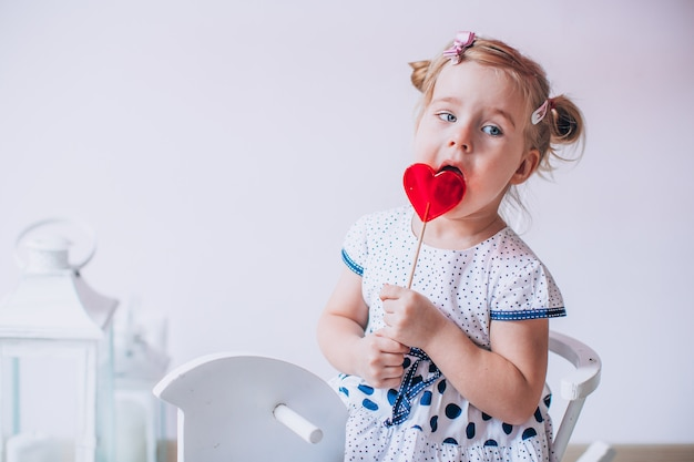 Adorable blonde girl eating a caramel lollypop in the shape of a heart. kid sitting on a white wooden horse