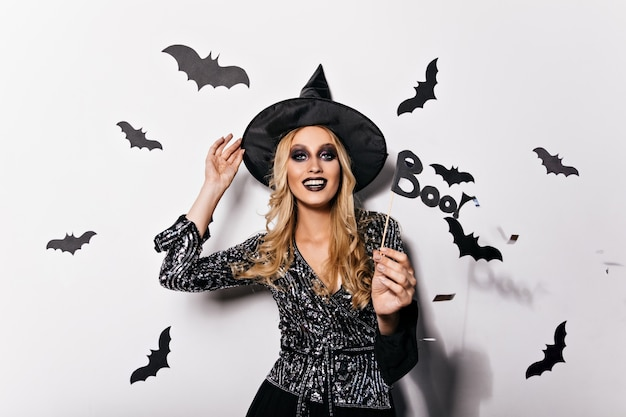 Прелестная блондинка в шляпе волшебника с удовольствием. фотография в помещении привлекательной кавказской леди, празднующей хэллоуин.