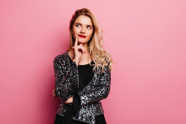 物思いにふける表情でポーズをとる愛らしいブロンドの女の子。ピンクの壁に立っているスパークルジャケットのかなり若い女性。