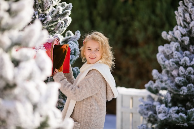 Adorable blonde girl sending her letter to santa, christmas time