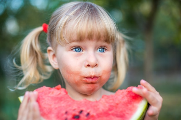 Adorable blonde girl with blue eyes eats a slice of watermelon outdoors