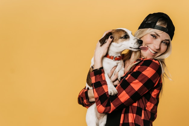 野球帽とチェックシャツを着た愛らしいブロンド、広い笑みを浮かべて、黄色の背景に彼女の子犬のジャックラッセルを頬をなめます。ペットとホスト。幸福の概念。