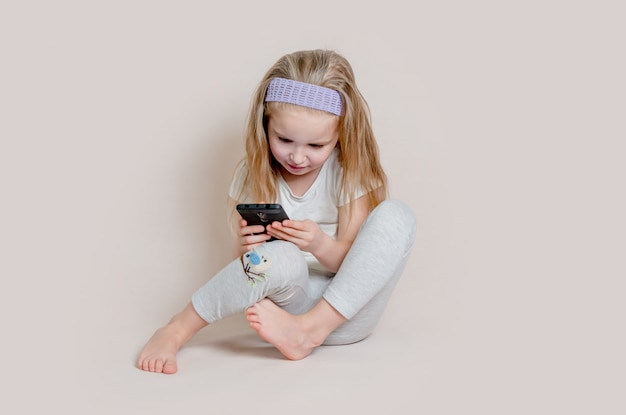 Adorable blonde little girl in pajamas playing with smartphone sitting on the floor