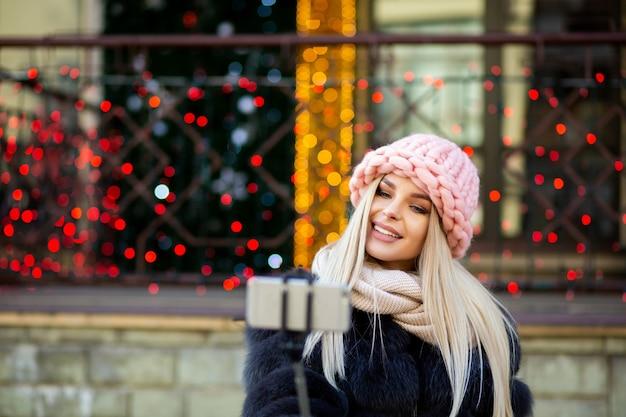 ピンクの帽子をかぶって、花輪で飾られた街の通りで自分撮りをしている愛らしい金髪モデル。テキスト用のスペース