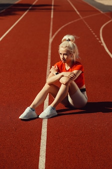 Очаровательная блондинка сидит на беговой дорожке