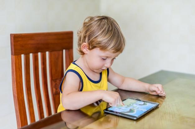 デジタルタブレットで遊ぶ愛らしい金髪幼児男の子