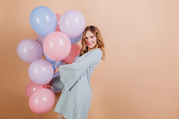 Adorable blonde white woman in blue attire posing with beautiful balloons