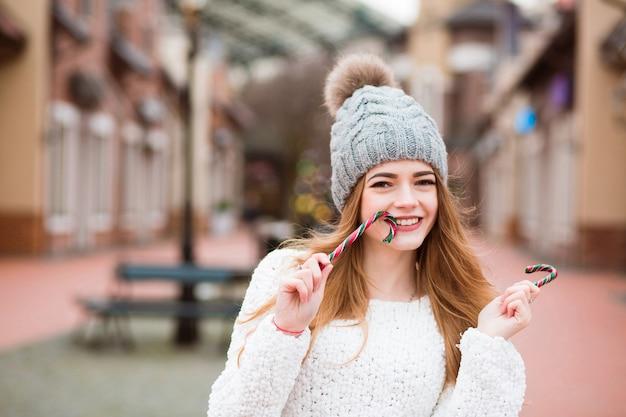 通りでクリスマスのキャンディケインを楽しんでいる愛らしいブロンドの女性の女の子