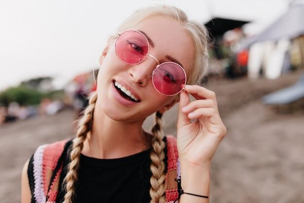 ビーチでポーズをとってピンクのメガネに触れる愛らしいブロンドの女性。