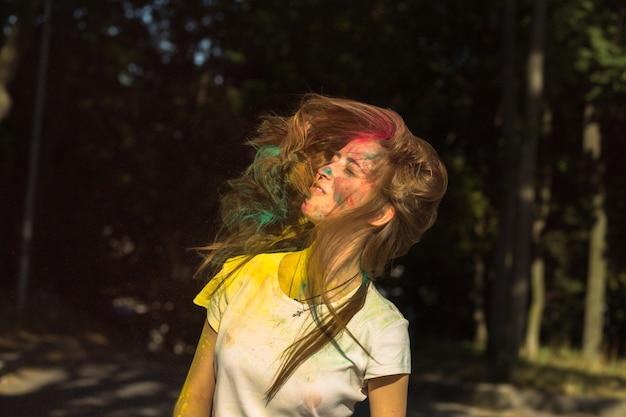 ホーリー祭を祝う空飛ぶ髪の愛らしいブロンドの女性