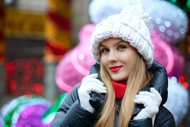 花輪の背景の上の通りで冬の休日を楽しんで赤い唇を持つ愛らしいブロンドの女性