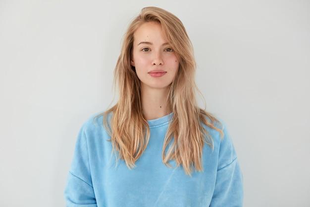 青いセーターを着た真面目な表情の愛らしい金髪女性は、白い壁に隔離された健康で清潔な肌をしています。きれいな女性は彼女の自然の美しさを示しています