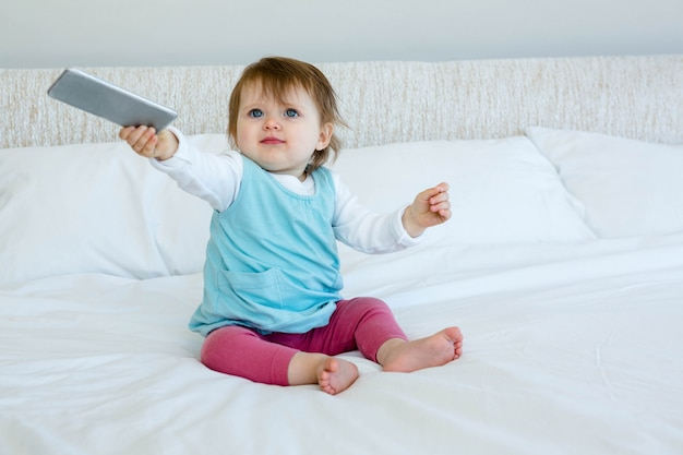 Adorable blue eyed baby sitting on a bed, holding out a mobile phone