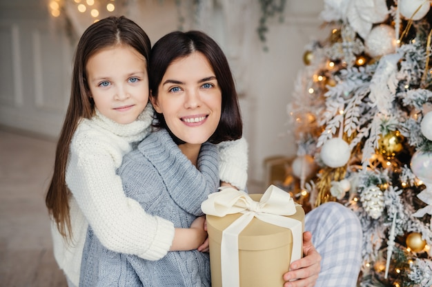 Adorable blue eyed small kid huggs with great love her mother who holds wrapped gift box, stand near decorated christmas tree, happy to celebrate winter holidays. people, celebration, presents concept