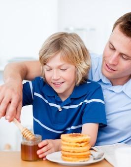 愛らしい少年と父親がワッフルに蜂蜜を入れている