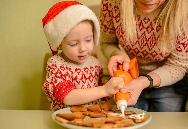 愛らしい男の子が自家製のお祝いジンジャーブレッドを焼きます。面白い子供はサンタクロースのために休日の食べ物を準備します。