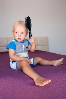 愛らしい男の子が髪を磨きます。かわいい赤ちゃんが楽しんで、ヘアブラシを持って髪をとかします。