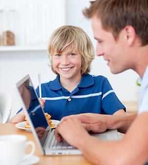 ラップトップを使用している彼の父親の間に朝食を持っている愛らしい少年