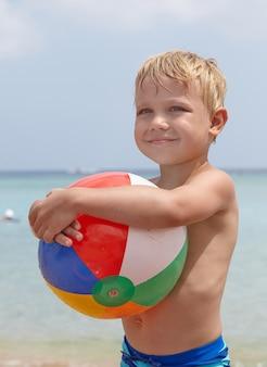 Adorable boy holding ball on the beach