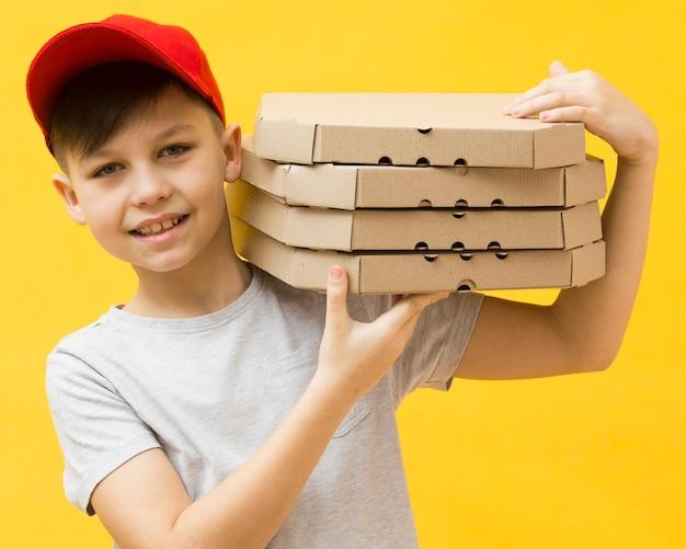 Прелестный мальчик держит коробки для пиццы