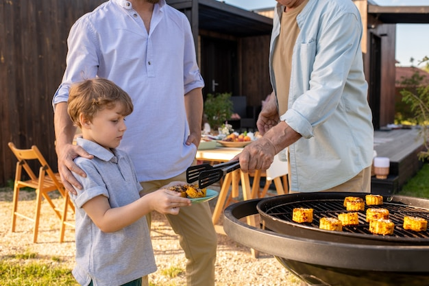Adorable boy holding plate while his grandfather putting him grilled corn