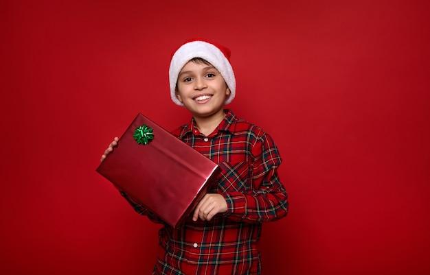 Очаровательный мальчик в шляпе санты и клетчатой рубашке держит рождественский подарок в блестящей подарочной бумаге с зеленым бантом, улыбается зубастой улыбкой, глядя в камеру, позирует на цветном фоне. копировать пространство