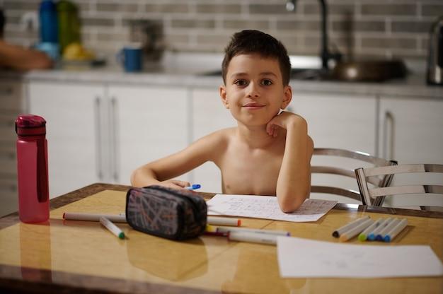 테이블에 앉아 집에서 그림을 그리는 동안 카메라를 보고 있는 사랑스러운 소년