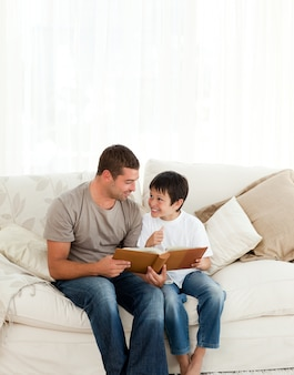 Adorable boy looking at a photo album with his father on the sofa