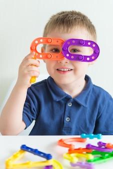 Очаровательный мальчик сделал очки из пластиковой игрушки и улыбается. вертикальное фото забавного малыша