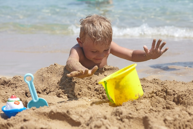 愛らしい少年は砂でビーチで遊ぶ