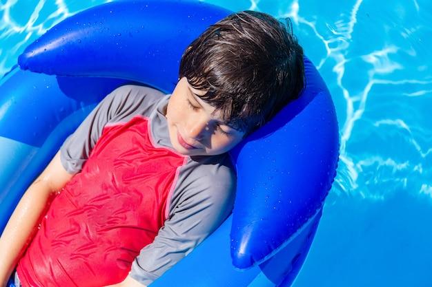 膨脹可能なマットレスのプールで休んでいる愛らしい少年