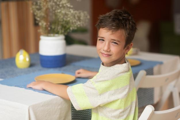 Очаровательный мальчик сидит за обеденным столом в ожидании еды, глядя на рамку в полоборота