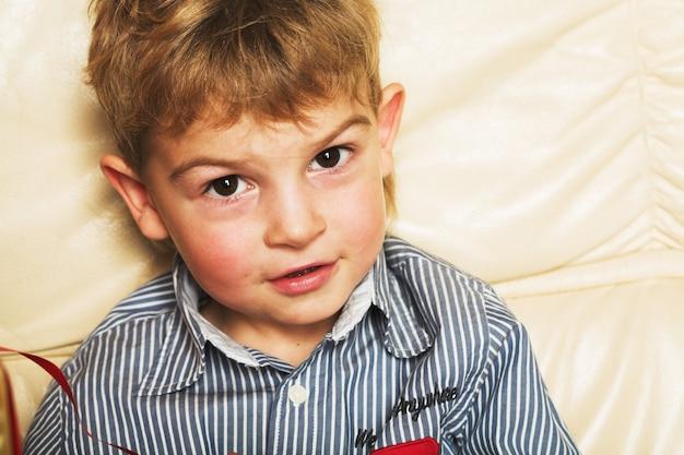 Adorable boy sitting on sofa